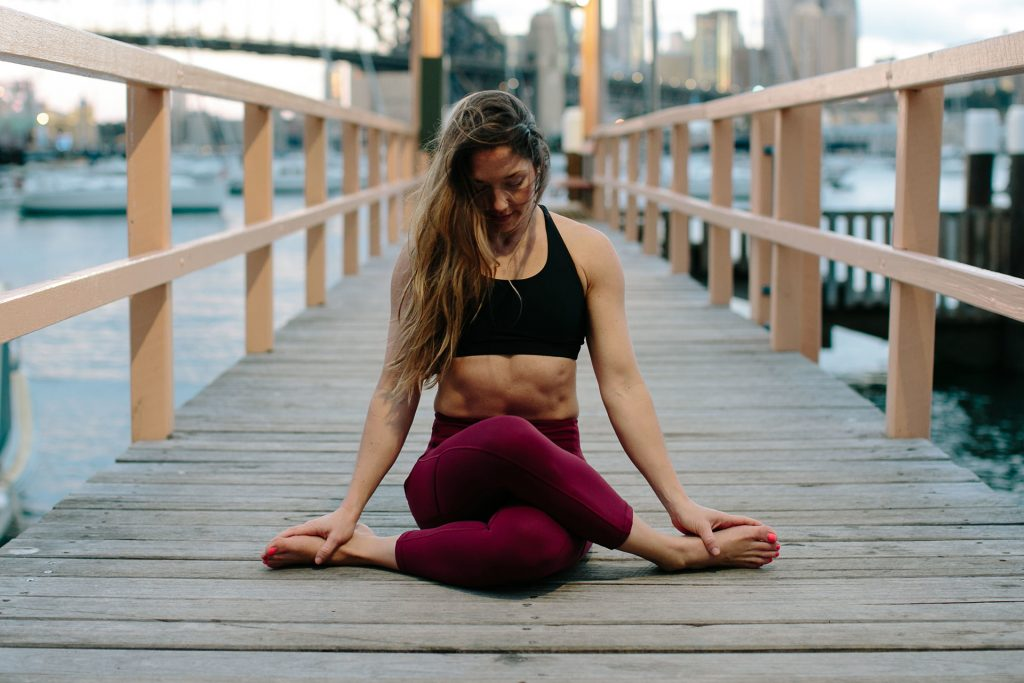 Kat Clayton in meditation seated yoga pose in red pants
