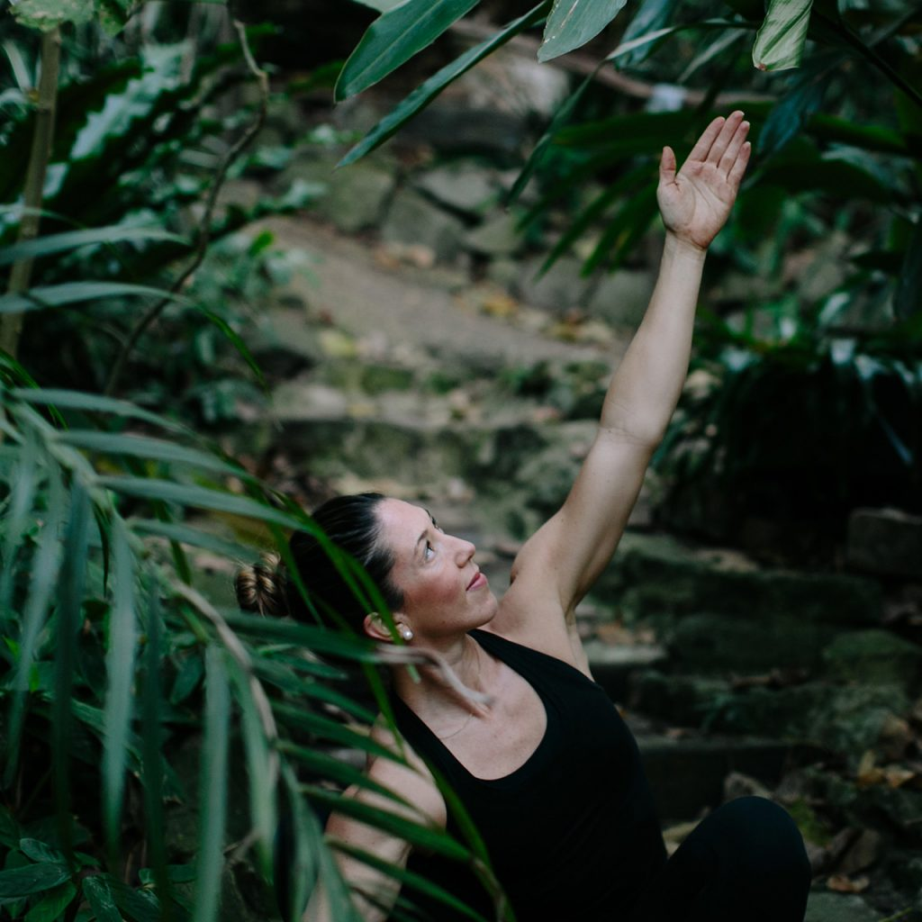 Girl doing yoga in Nature with palm trees