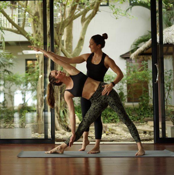 Kat Clayton assisting yoga student at Thailand Yoga Retreat