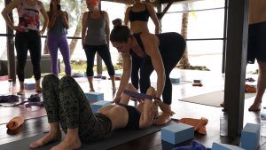 Kat Clayton assisting a yoga student into wheel pose, teaching a yoga workshop on a yoga retreat in Thailand at Samhita Wellness and Yoga Retreat Centre