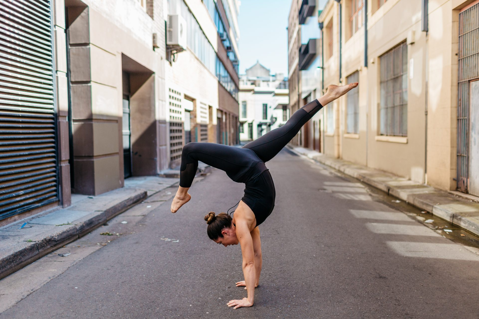 Kat Clayton doing a yoga pose handstand arm balance in an urban city environment Yoga Teacher Kat teaches workshops to learn how to handstand and armbalance