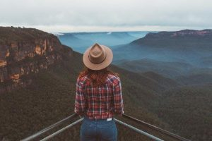 Girl looking out over the blue mountains with a hat