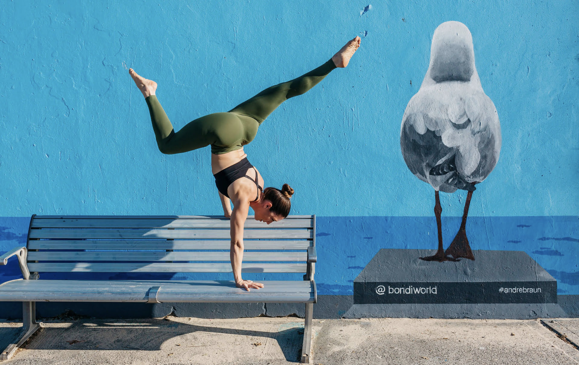 Kat Clayton Yoga arm balance on bench in Bondi
